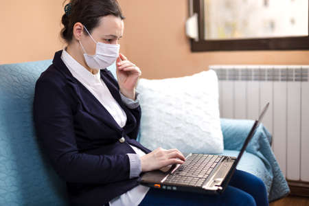 Woman with medical mask working on laptop, at home, concept of home working during quarantine Stock fotó