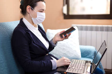 Woman with medical mask working from home, concept of home working during quarantine period Stock fotó