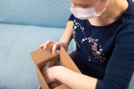 Woman with mask in medical self isolation opens her package. Concept of the quarantined person who orders and receives products online. Quarantined virus protection. Focus on hands. Place for text.
