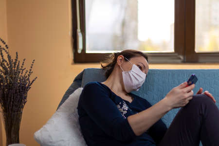 Depressed woman with medical mask sitting on sofa and looking in her smartphone.  Concept of quarantined during the pandemic and feeling the lack of socialization