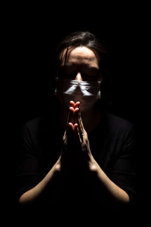 Woman with medical mask standing in prayer in dark background. Concept of infected person standing and praying in a creative light