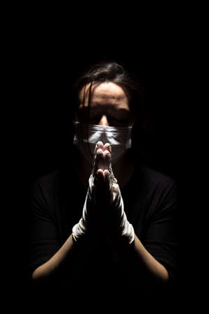 Woman with medical mask and gloves is prayer. Concept of infected person standing and praying in a creative light