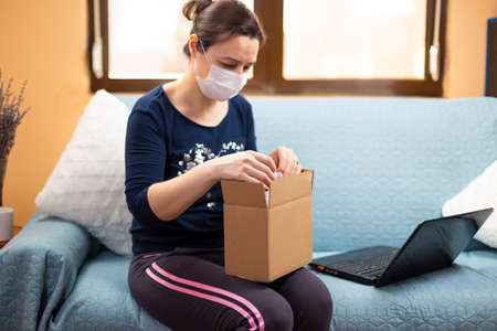 Woman with mask in medical self isolation opens her package ordered online. Concept of the quarantined person who orders and receives products online. Quarantined virus protection