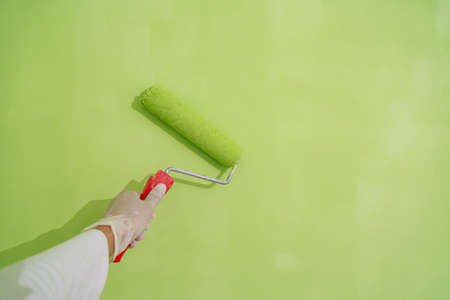 Painter with painting brush in hand painting a wall green Stock fotó