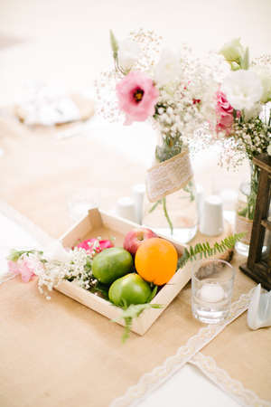 Wedding dining table and colorful flowers. Wedding day and wedding dining table. Fruit basket, apple, orange, lime. Stock Photo