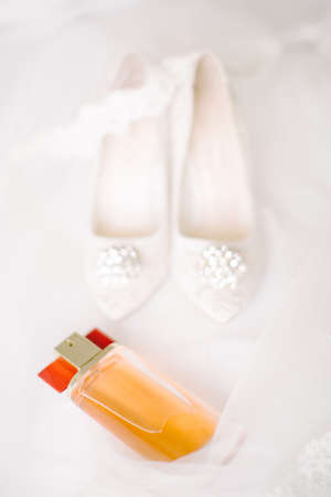Bridal shoes on tulle. Gemstone and lace. Perfume bottle.