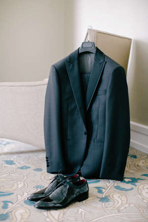 Groom suit and black groom shoes. Indoor and medium angle. Wedding preparations.