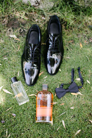 Groom accessories. Bow tie, shoes, perfume, whiskey. On the grass. Stock Photo