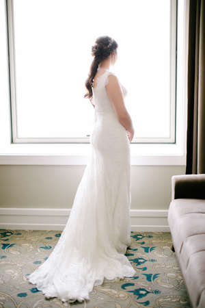 The bride poses facing back. He looks out the window. Indoor.