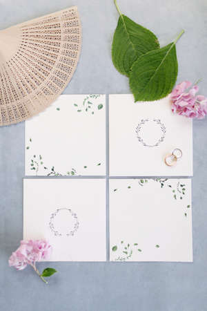 Wedding invitation. Empty white floor. Wedding rings. Fan and purple flowers. On the blue backdrop.