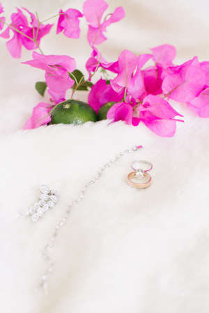 Wedding rings and jewelry. On a white background and pink bougainvillea leaves and lime. Stock Photo
