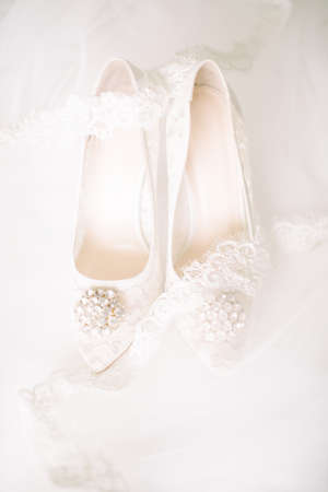 Bridal shoes on tulle. Gemstone and lace. Stock Photo