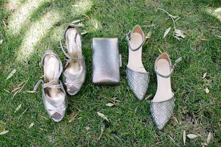 Gray heels and gray shiny handbag. On the grass.