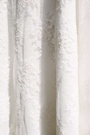 A white wedding dress hanged on the hanger. Preparations for the wedding day. Stock Photo