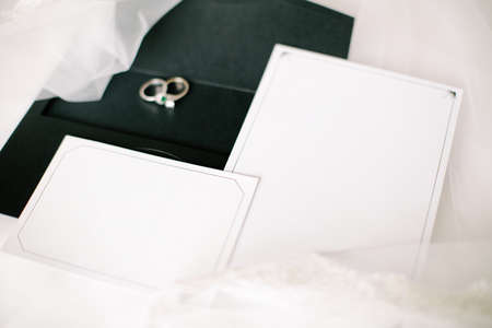 Wedding or engagement invitation. Empty white writing area. Wedding rings. Tulle on a floor.