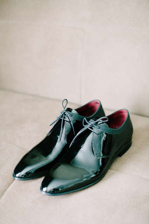 Black patent leather wedding shoes. Wedding reparations details. Indoor and close up.