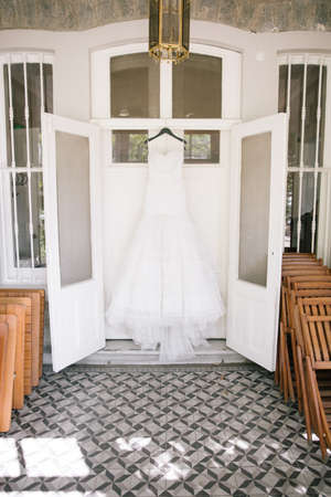 A wedding dress hanging on the door. Wedding dress in the winter garden. White and pure.