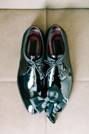 Black patent leather wedding shoes. Bow tie. Wedding reparations details. Indoor and close up.