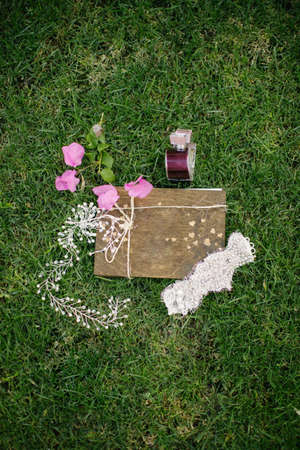 Wedding accessories. On the grass. Perfume, headband and notepad.