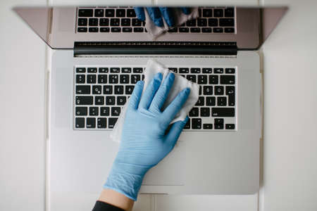 The woman cleans the keyboard of her computer to protect it from coronavirus. She uses the cleaning cloth and mitt.