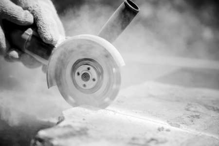 stone cutter: grinder worker cuts a stone the electric tool