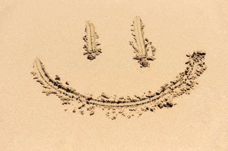 A smiley face drawing on a sand