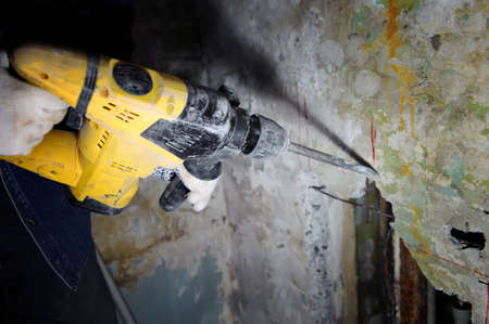 making hole: Construction worker making hole a using pneumatic hammer