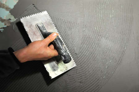 placing: Master puts adhesive on old wall Stock Photo