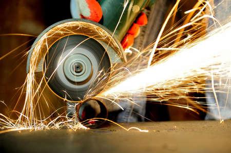 Pracownik cięcia metalu z młynka. Iskier podczas szlifowania żelaza