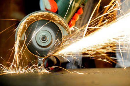 Worker cutting metal with grinder. Sparks while grinding iron Reklamní fotografie - 37167808