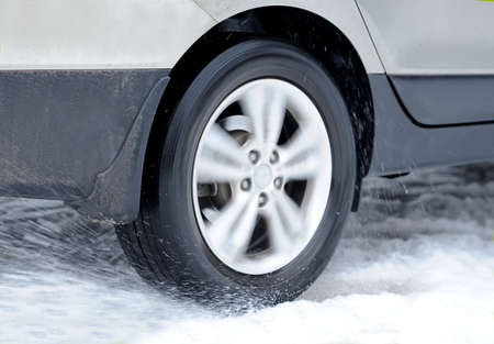 Dirty car wheel stands on winter snowy road photo