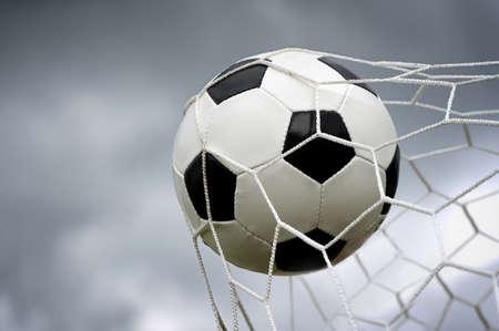 Football. The ball flies into the net gate photo
