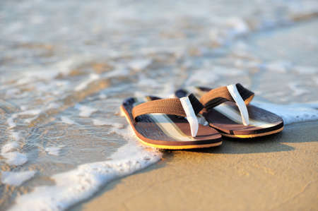 flip flop: Summer vacation concept. Flip flops on a sandy ocean beach