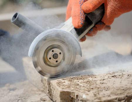 travailleur de broyage coupe une pierre l'outil électrique