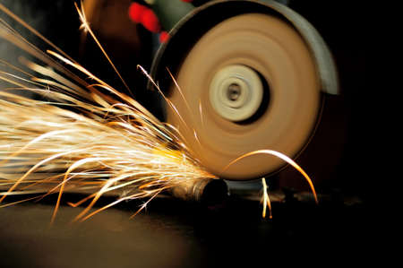 cutting metal: Worker cutting metal with grinder. Sparks while grinding iron