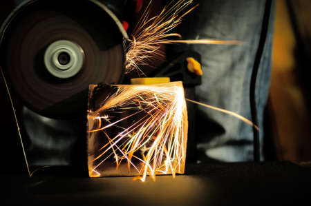 tool and die: Worker cutting metal with grinder. Sparks while grinding iron