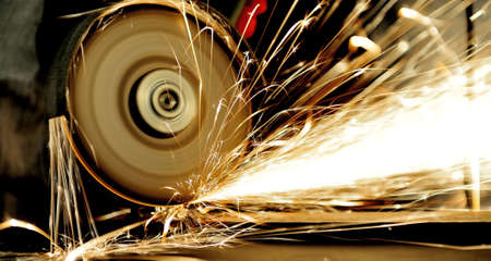 Worker cutting metal with grinder. Sparks while grinding iron photo