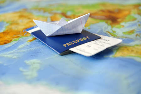 passport background: Paper boat, passport on a background map of the world. Traveling concept