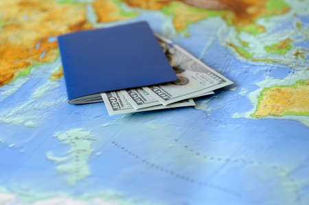 Passport and money on a background map of the world. Traveling concept photo