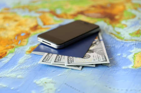 Phone, passport, money on a background map of the world. Traveling concept photo