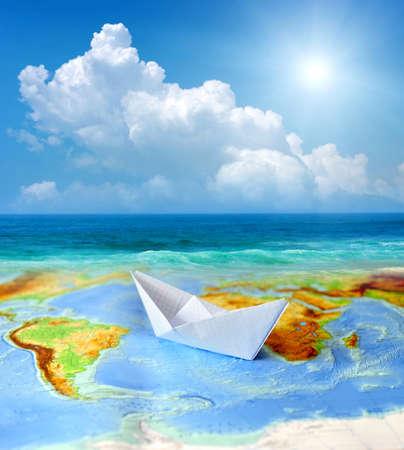 Paper boat sur un fond de carte du monde. Notion Voyager