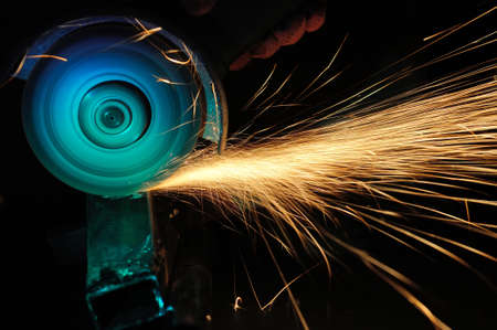 Worker cutting metal with grinder. Sparks while grinding iron Фото со стока - 38877875
