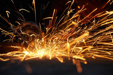 Worker cutting metal with grinder. Sparks while grinding iron Imagens - 38877772