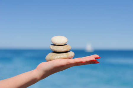 destress: Stones in a hand on a background of the dark blue sky