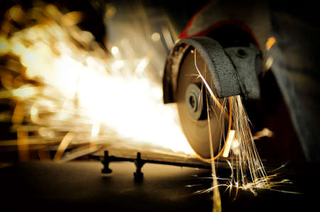 Worker cutting metal with grinder. Sparks while grinding iron Imagens - 40040311