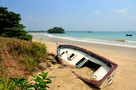 beached: Old yacht stranded on a beach after storms in ocean