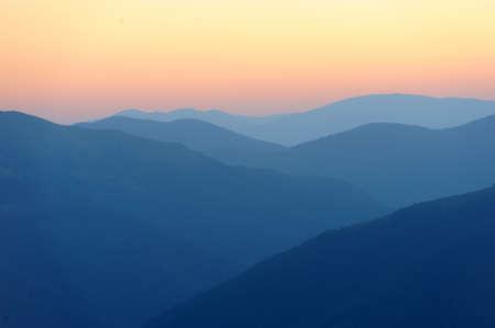 山のシルエットと山脈の美しい日の出