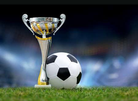 trofeo: Trofeo de oro en la hierba en el fondo del campo de fútbol Foto de archivo