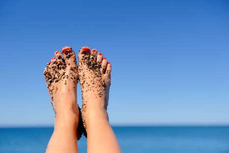 Vacanze vacanze. Piedi della donna del primo piano della ragazza di relax sulla spiaggia