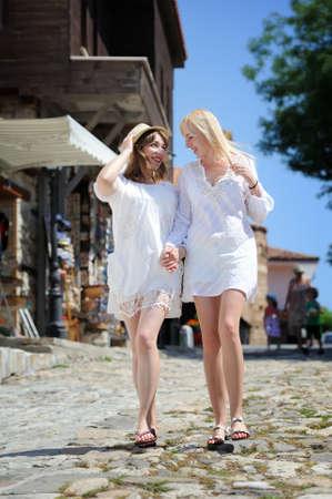 weisse kleider: Zwei M�dchen in wei�en Kleidern zu Fu� in der alten Stra�e